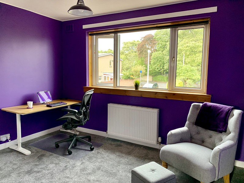 My new office, wide view with desk and armchair both visible. Purple walls. Dark grey carpet.