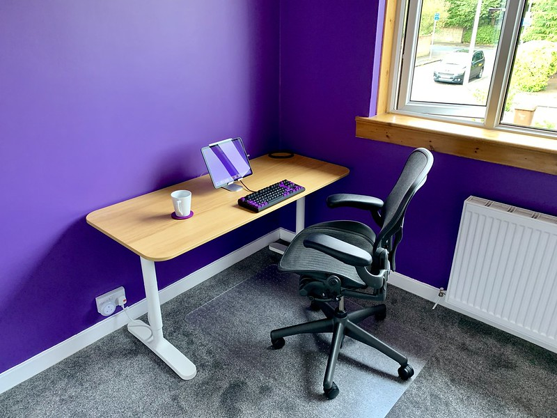 View of desk with purple felt coaster holding a white ceramic coffee mug.