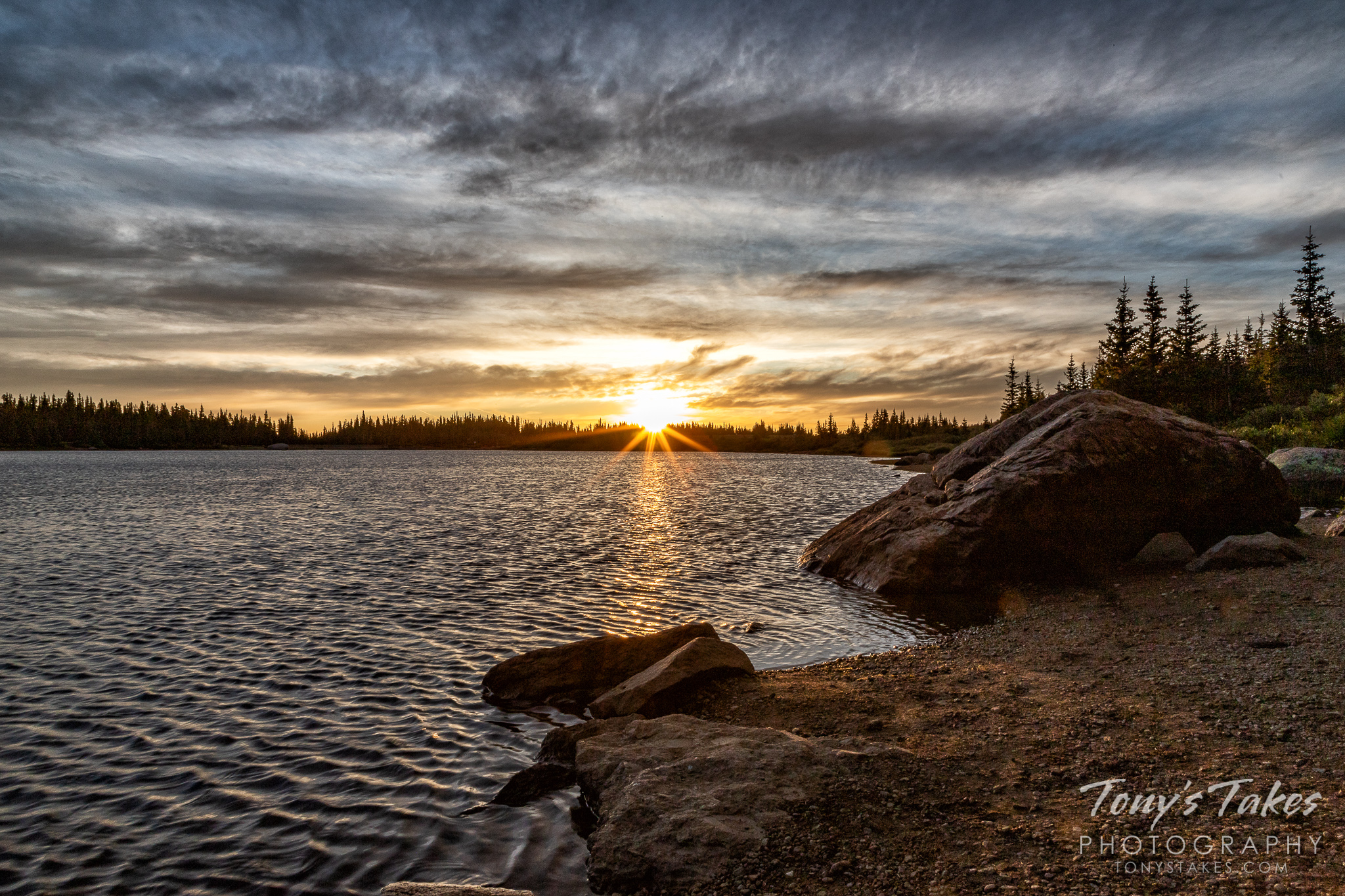 The sun rises over the horizon at Brainard Lake in Colorado. (© Tony's Takes)