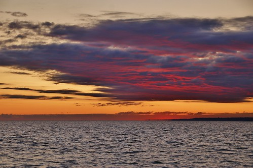 sky clouds greys blues black orange red water waves layers evening lightedundersides firelike summer sunset pink