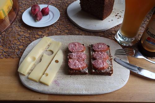 Käsescheiben zu aufgeschnittenem Bierknacker auf Schwarzbrot