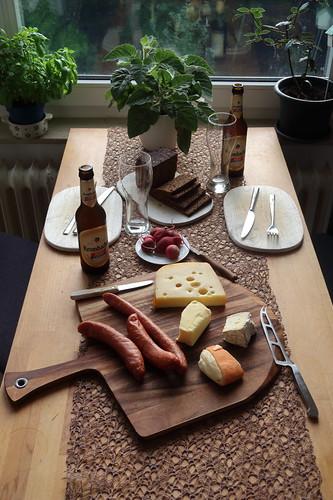 Abendbrot mit diversen Käsesorten, Bierknackern, Schwarzbrot, Radieschen, Salatgurke und alkoholfreiem Weizen