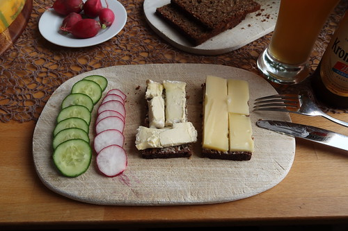 Käse auf Schwarzbrot zu Radieschen und Salatgurke