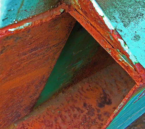 Contrast of orange rust and sea green on a dumpster