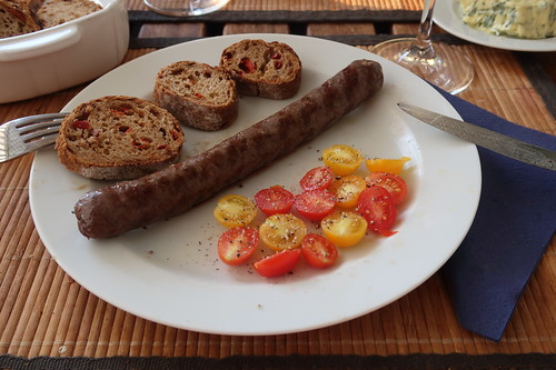 Rindsbratwürstchen mit Oliven-Peperoni-Baguette und kleinen Tomaten