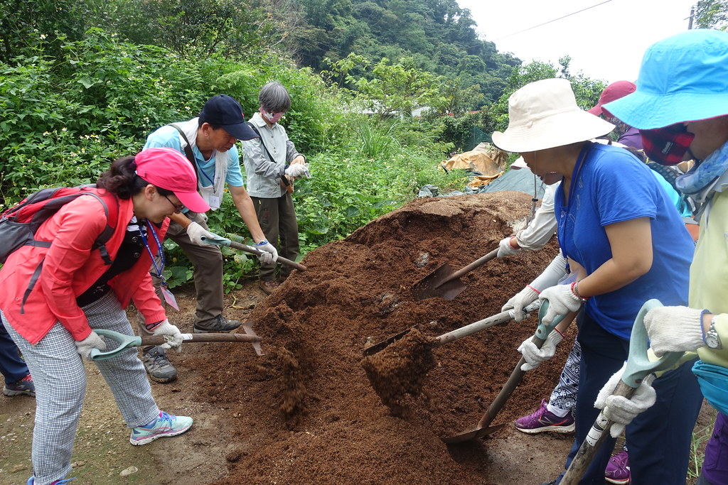 學員們協力翻堆肥。攝影:許芷榕