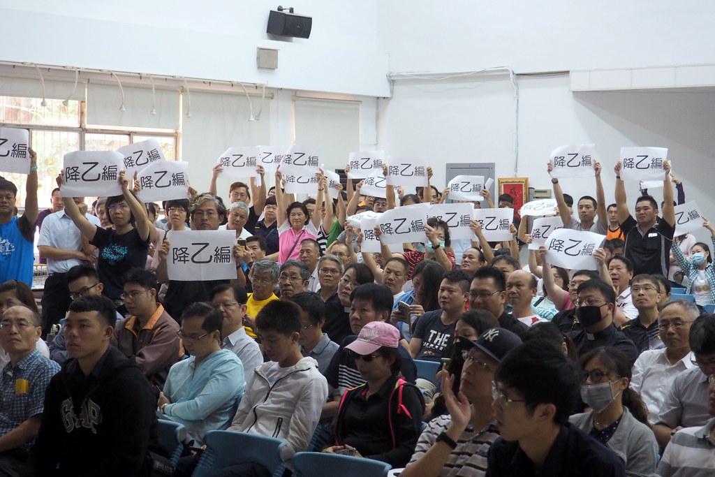 居民高舉「降乙編」標語,抗議廠商說法,表達訴求。前方座位者為廠商員工。攝影:李育琴