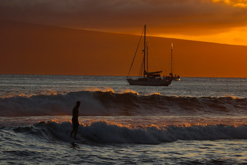 Surfing in Maui at sunset