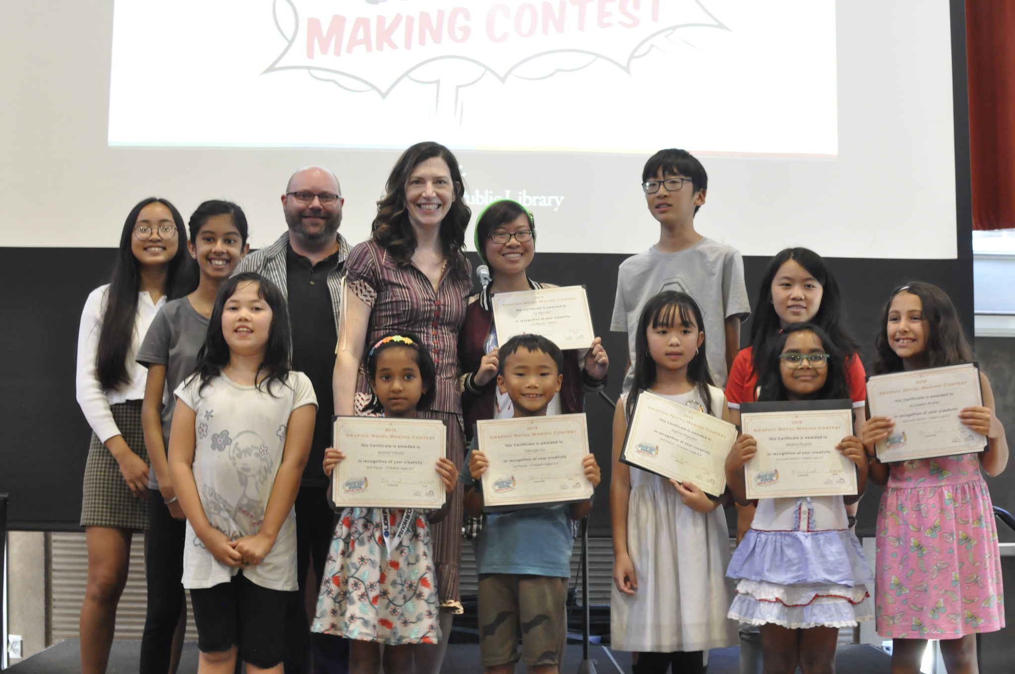 Winners of the library's 2019 Graphic Novel Making Contest standing on a stage with City Librarian Jill Bourne