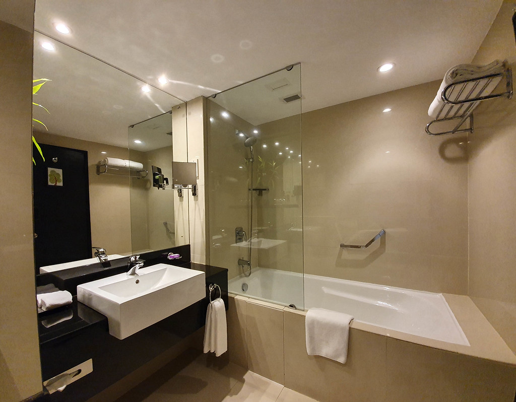 The cream and dark brown designed bathroom with a sink on the left and a big bathtub on the right