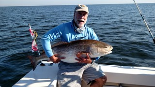 Photo of man holding a large red drum he caught
