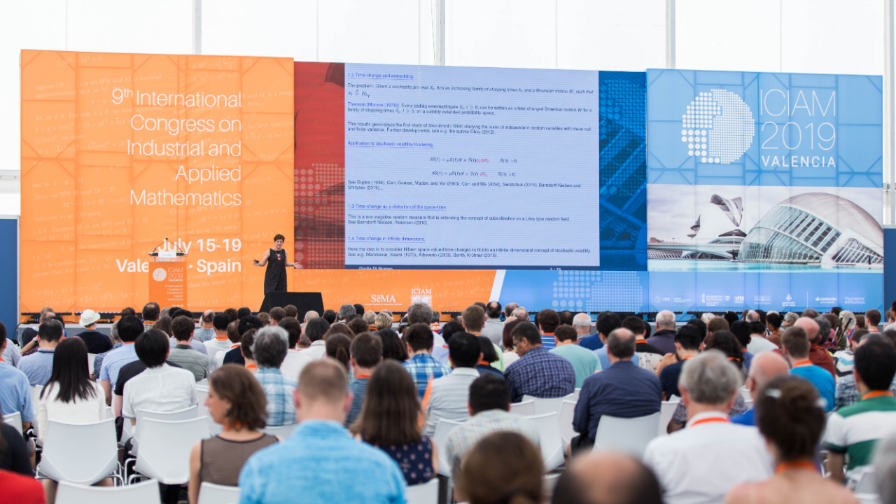 Woman giving a plenary talk to a large crowd at the 2019 International Congress on Industrial and Applied Mathematics