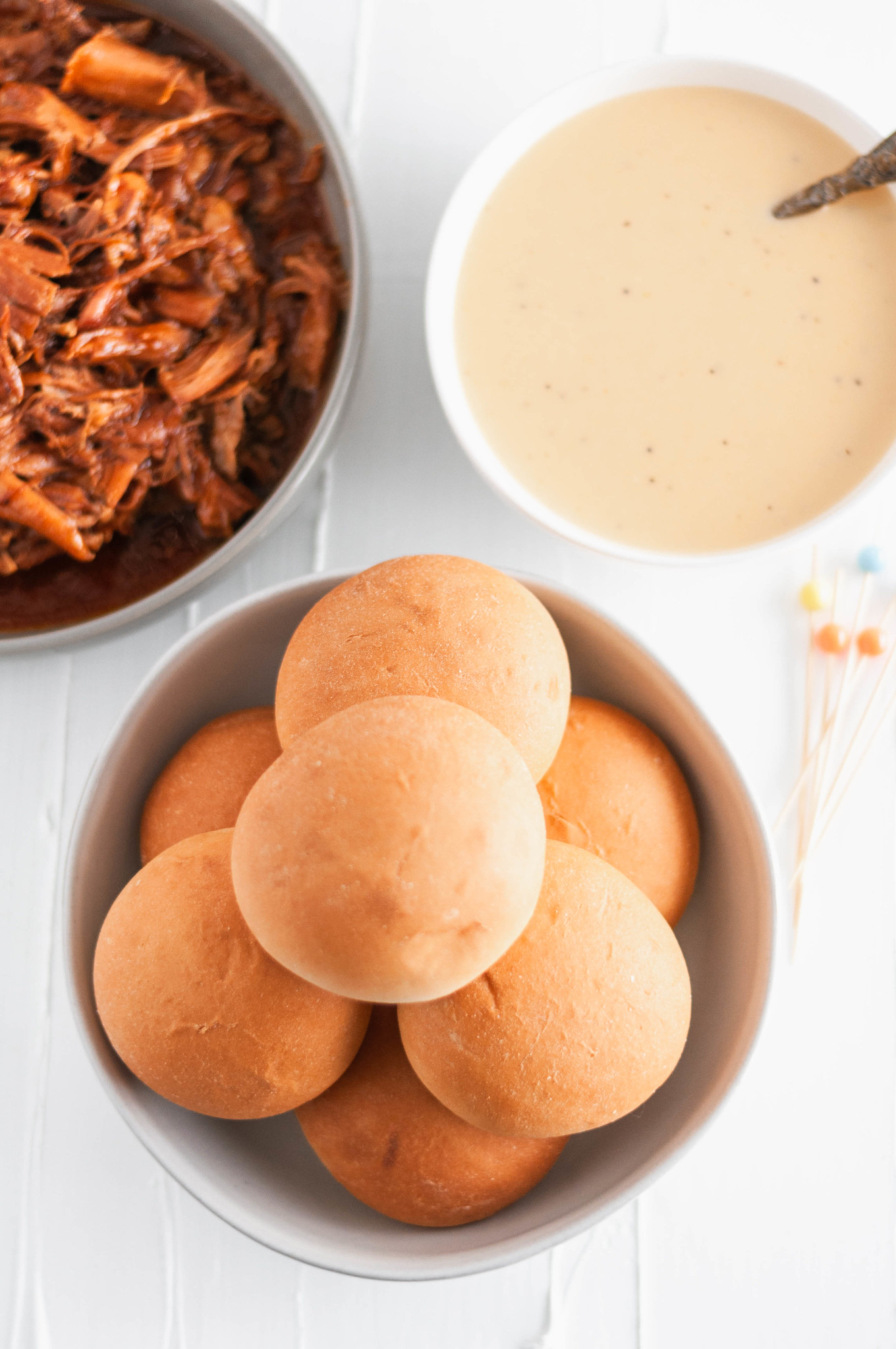 It's football season and that means we need all the delicious party food. Start the game off right with these Cheesy Pulled Pork Sliders. Slow cooker pulled pork, barbecue sauce and a rich, cheesy sauce all loaded atop a soft, pillowy Rhodes Warm-N-Serv roll.