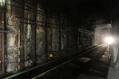 Headlights of an approaching train illuminate the tunnel at Mong Kok