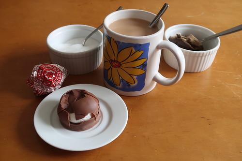 mit einer dünnen Schicht Vollmilchschokolade überzogener Baiser auf Bisquitboden (Tunnock's Tea Cake) zu englischem Tee mit Milch und Zucker