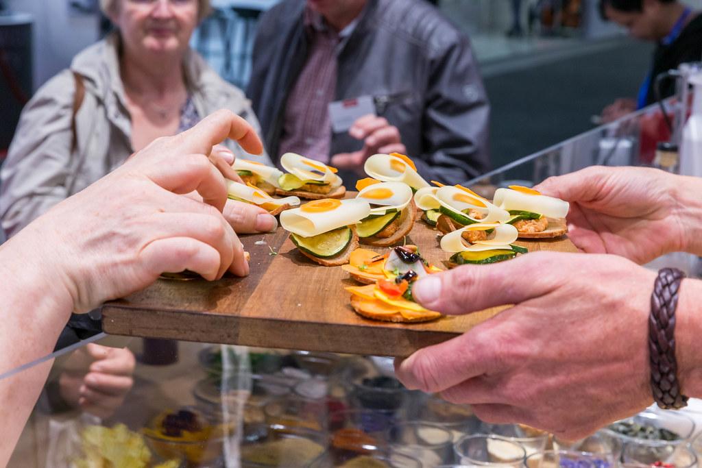 Messekoch überreicht Fingerfood auf einem Holzbrettchen auf der IFA
