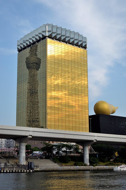 Asahi beer headquarters reflecting Skytree on one side and bright clouds on the other