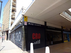 """The corner of a small shopping parade, with pavements running along both sides.  Black shutters are down over the unit on the corner, with """"CR0"""" painted on them.  The skeleton of a tower block rises up behind."""