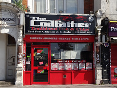 """A small terraced shopfront with a red frame and riser, and a rather over-dramatic sign in black, red, and white, reading """"The Codfather / Traditional Fish & Chips / Peri Peri Chicken & Kebabs"""".  Decals advertising """"Meal Deals"""" cover much of the window."""