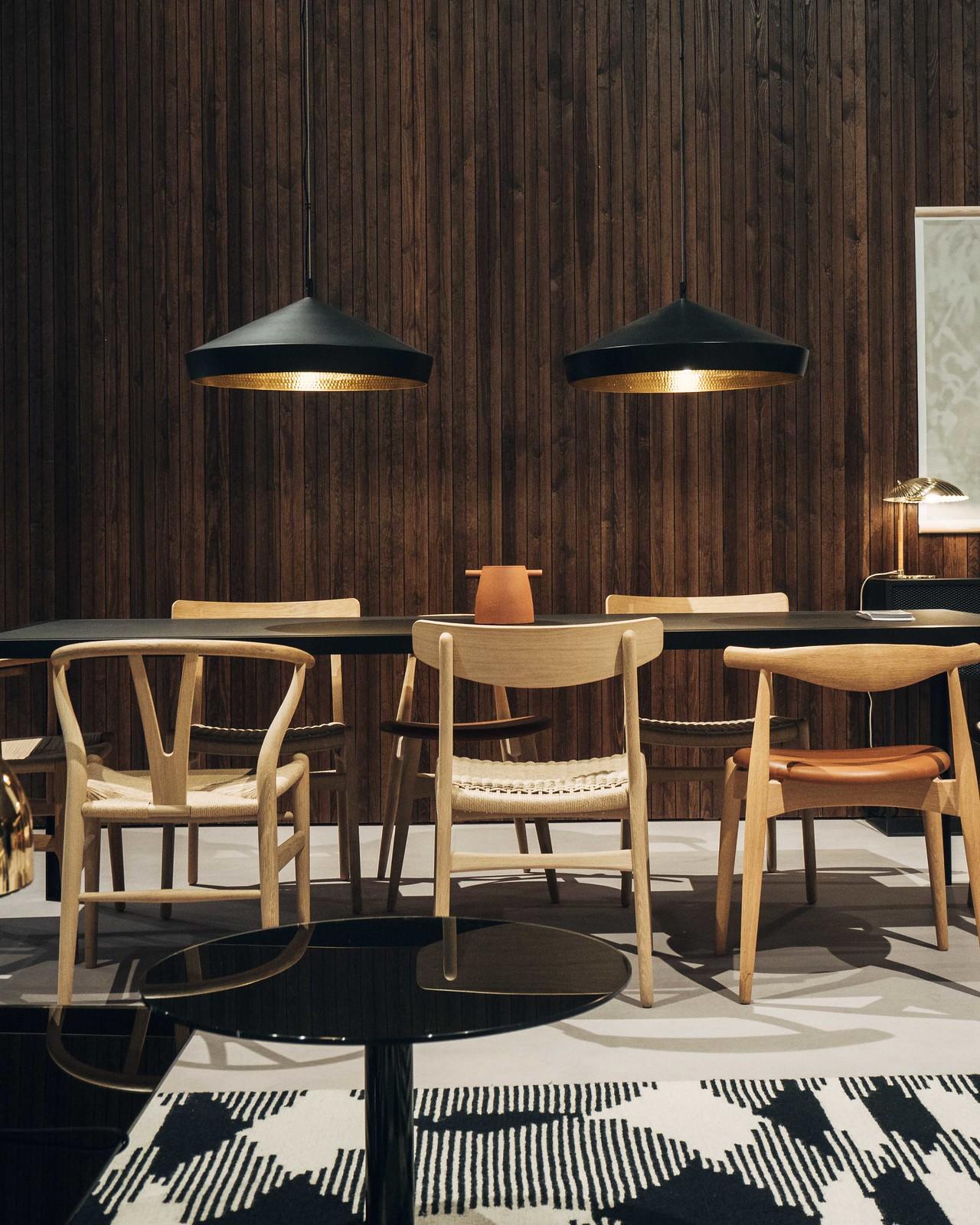 Ruokailuryhmä tummaa puuseinää vasten. Ruokapöydän yläpuolella roikkuu kaksi mustaa valaisinta.