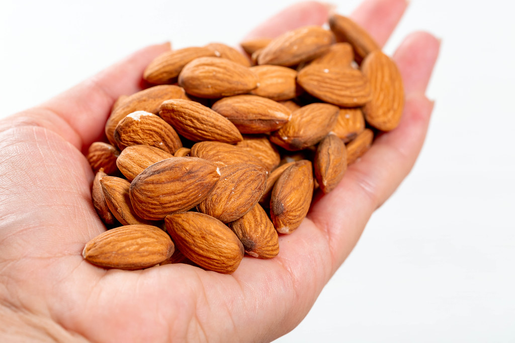 Female hand full of almonds nuts on white background | Flickr