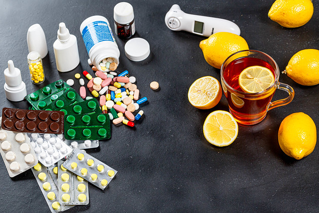 Colorful medicines and pills with a Cup of tea and lemons. Concept folk medicine and traditional medicine