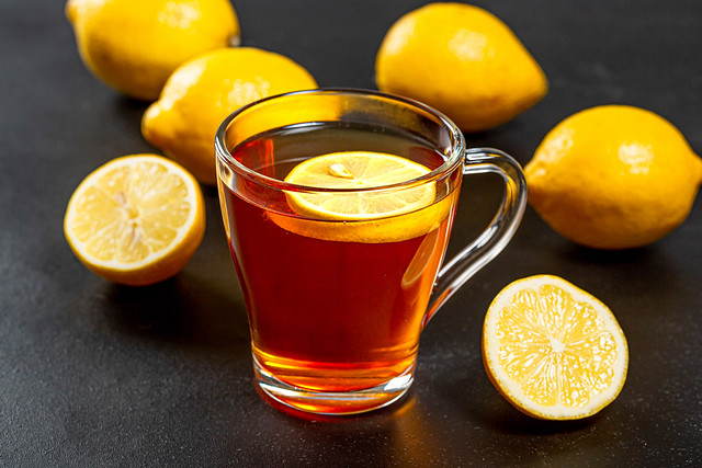 Hot tea with fresh yellow lemons on black background