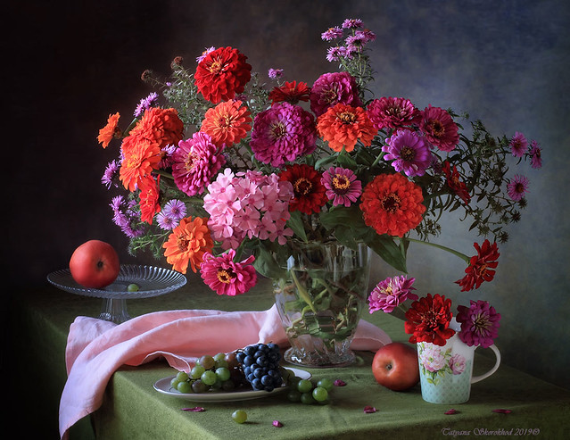 Still life with a bouquet of zinnia and grapes