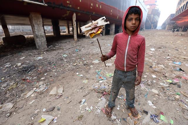 Bangladesh, street kid collects trash in Dhaka