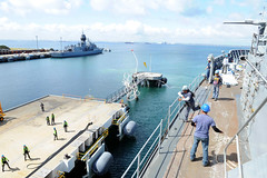 Able Seaman Genaro Cuico, a Military Sealift Command civilian mariner assigned to USS Emory S. Land (AS 39), tosses a line to the pier as the ship prepares to moor, Sept. 11. (U.S. Navy/MC3 Destinyy Reed)