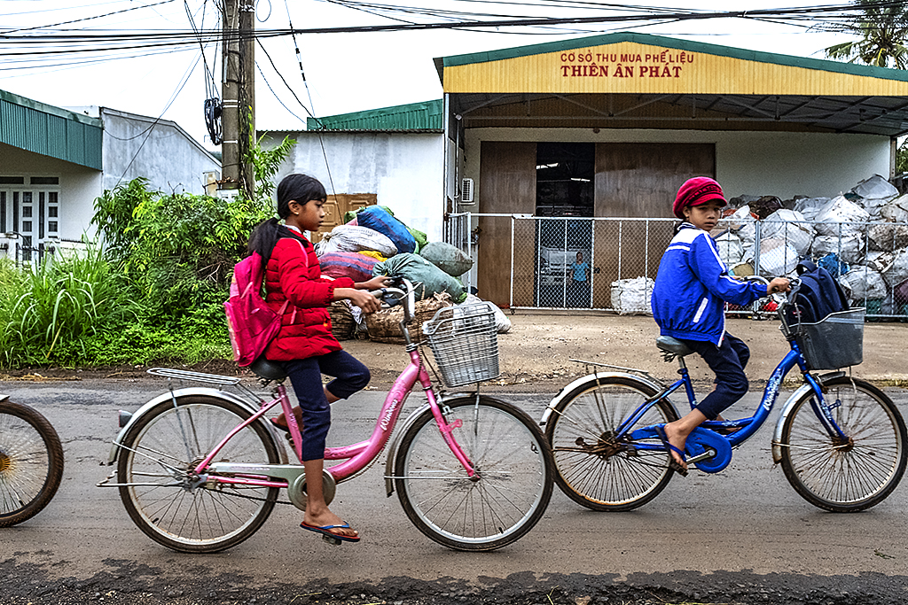 Girls cycling to school in front of plastic recycling plant--Ea Kly