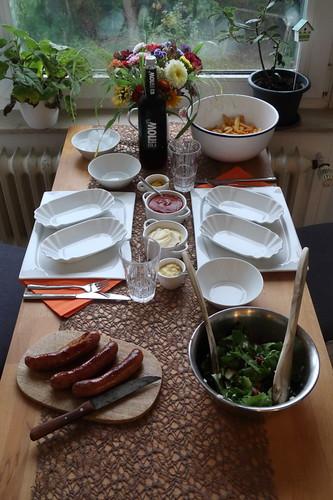 Krakauer mit Ketchup und Curry zu Pommes mit Mayonnaise und gemischtem Salat (Tischbild)