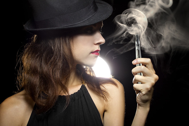 woman smoking or vaping an electronic cigarette to quit tobacco
