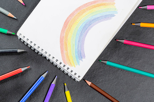 Painted rainbow in a notebook and a variety of colored pencils on a black background | by wuestenigel