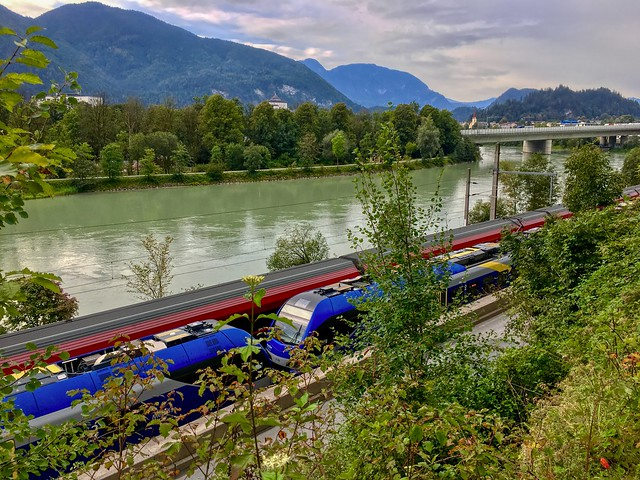 ÖBB railjet and Meridian express trains passing each other along the river Inn near Kufstein, Tyrol, Austria