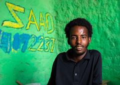 Young somali man in a shop with green walls, Sahil region, Berbera, Somaliland