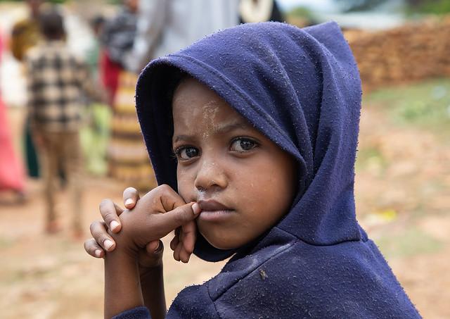 Oromo pilgrim boy in Sheikh Hussein shrine with jarawa powder on the face, Oromia, Sheik Hussein, Ethiopia