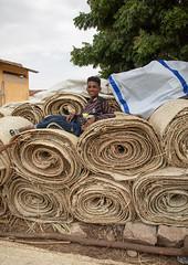 Eritrean boy sit on a stack of straw mats, Semien-Keih-Bahri, Keren, Eritrea