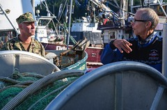 Rear Adm. Scott Gray, learns about local commercial fishing processes from John Renner, a commercial fisherman in Cordova, Alaska. (U.S. Navy/MCCS Brandon Raile)