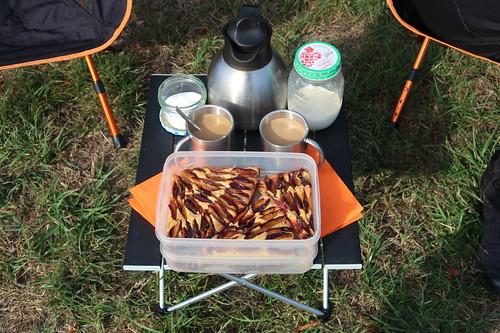 Schneller Zwetschgenkuchen und Kaffee mit Milch und Zucker (auf Picknicktisch)