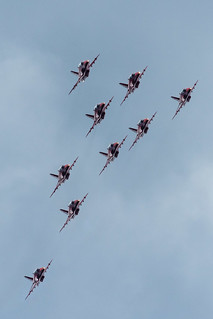 The Red Arrows bank around in tight formation with lights on