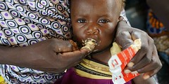 An infant of 9 months, with her mother Alima, eats high nutrient peanut paste as a distribution at the Guidanaoutchi Clinic, Niger.