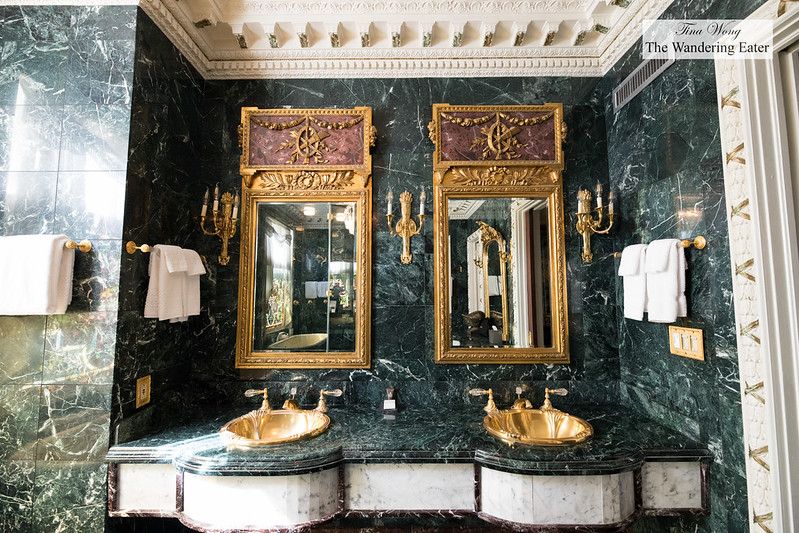Double sink vanity in an all green marble bathroom
