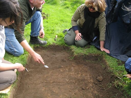 An archaeologist describes how to carefully excavate a body from a grave. You can just make out the slightly different colouration in the soil
