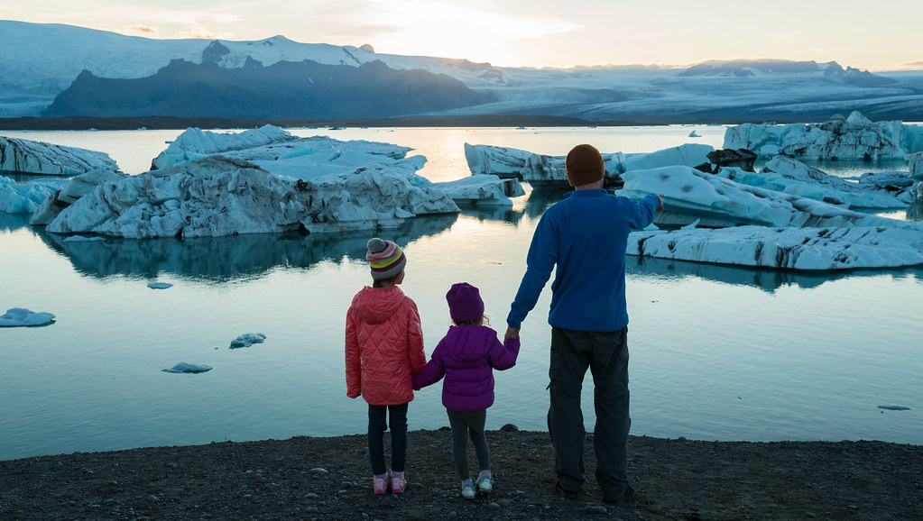 Father and daughters looking out on icebergs in the water at Jokulsarlon Lagoon