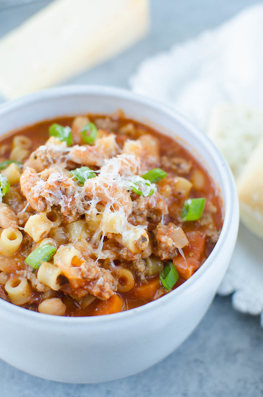 Pasta Fagioli - Olive Garden copycat recipe. This hearty soup is filled with spicy Italian sausage, veggies, pasta, and beans and topped with fresh shredded Parmesan cheese. It is serious comfort food that the whole family will love!