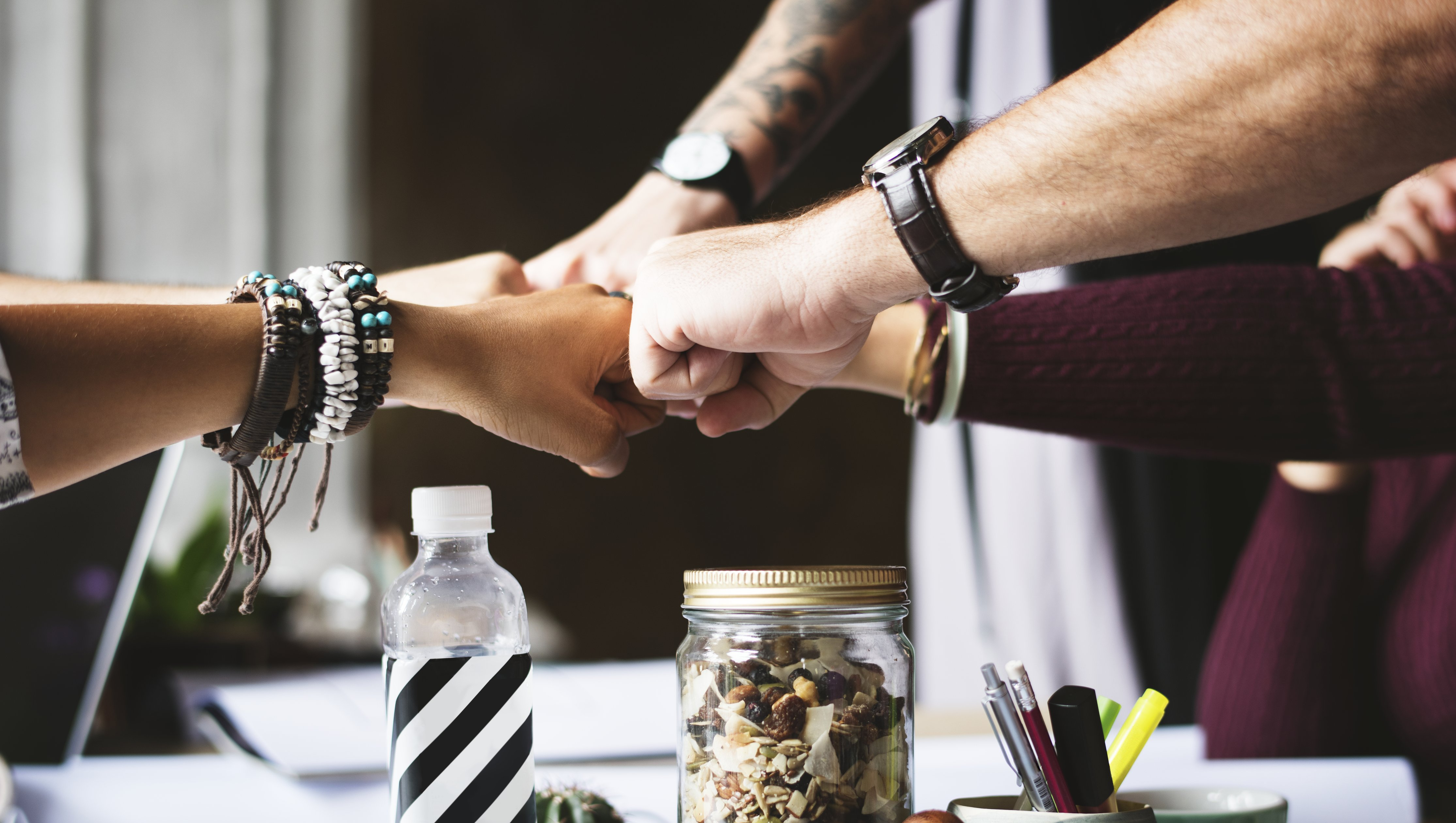 Business colleagues fistbumping over a desk