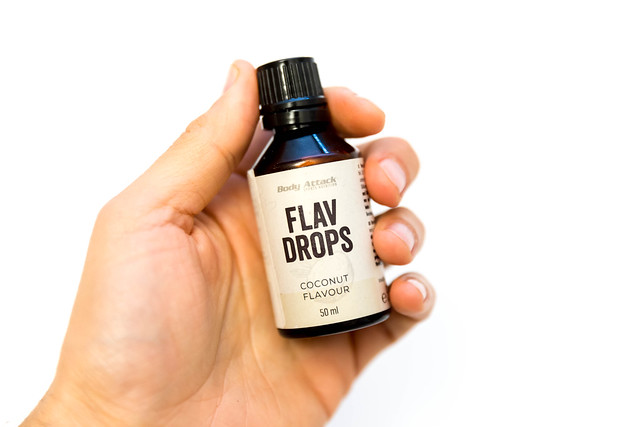 Hand holds aromatic Flav-Drops with coconut flavor by Body attack, for shakes and smoothies