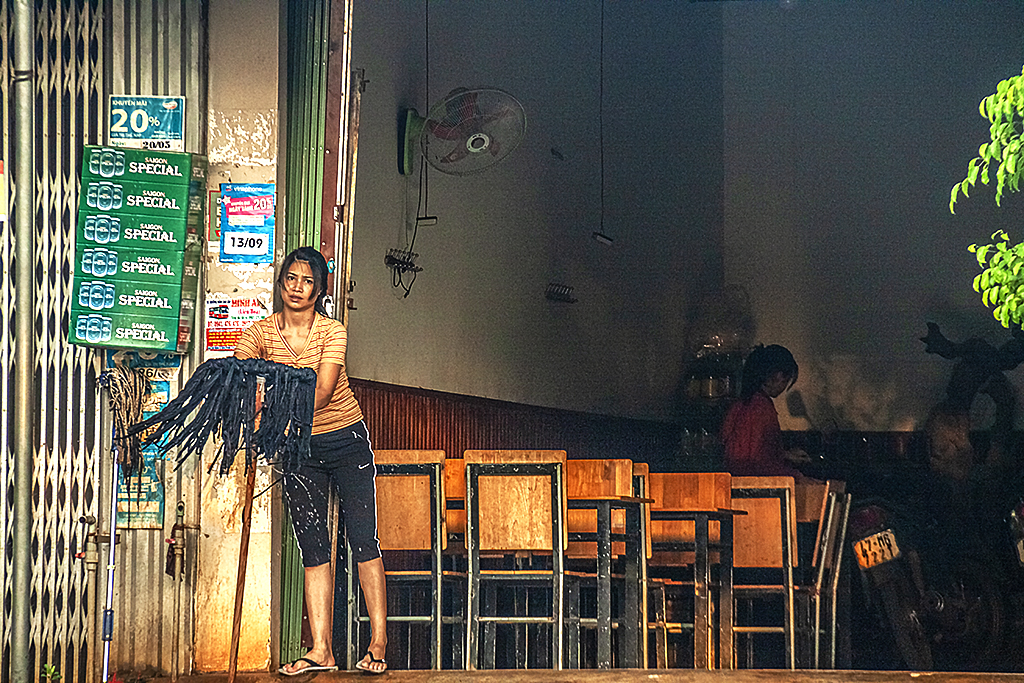 Woman mopping in front of her eatery--Ea Kly