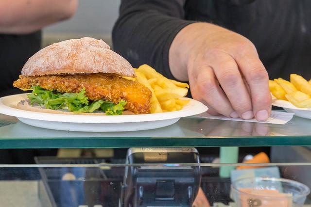 Hähnchenfilet-Burger im Knuspermantel mit Salat und Pommes Frites auf einer Glastheke